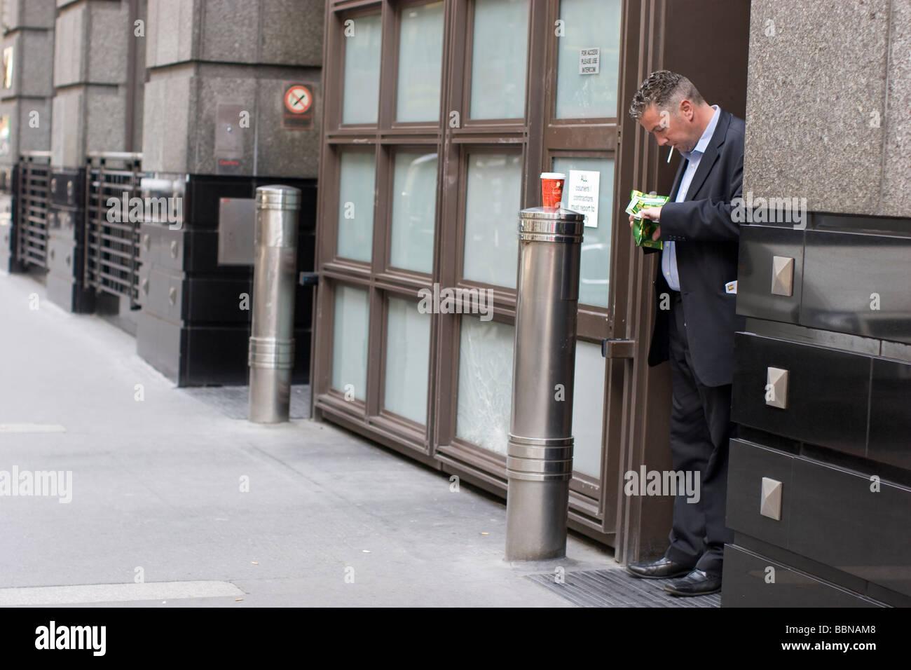 roll up, city worker Smoker in doorway London UK smoker rolling up cigarette in doorway in London street - Stock Image