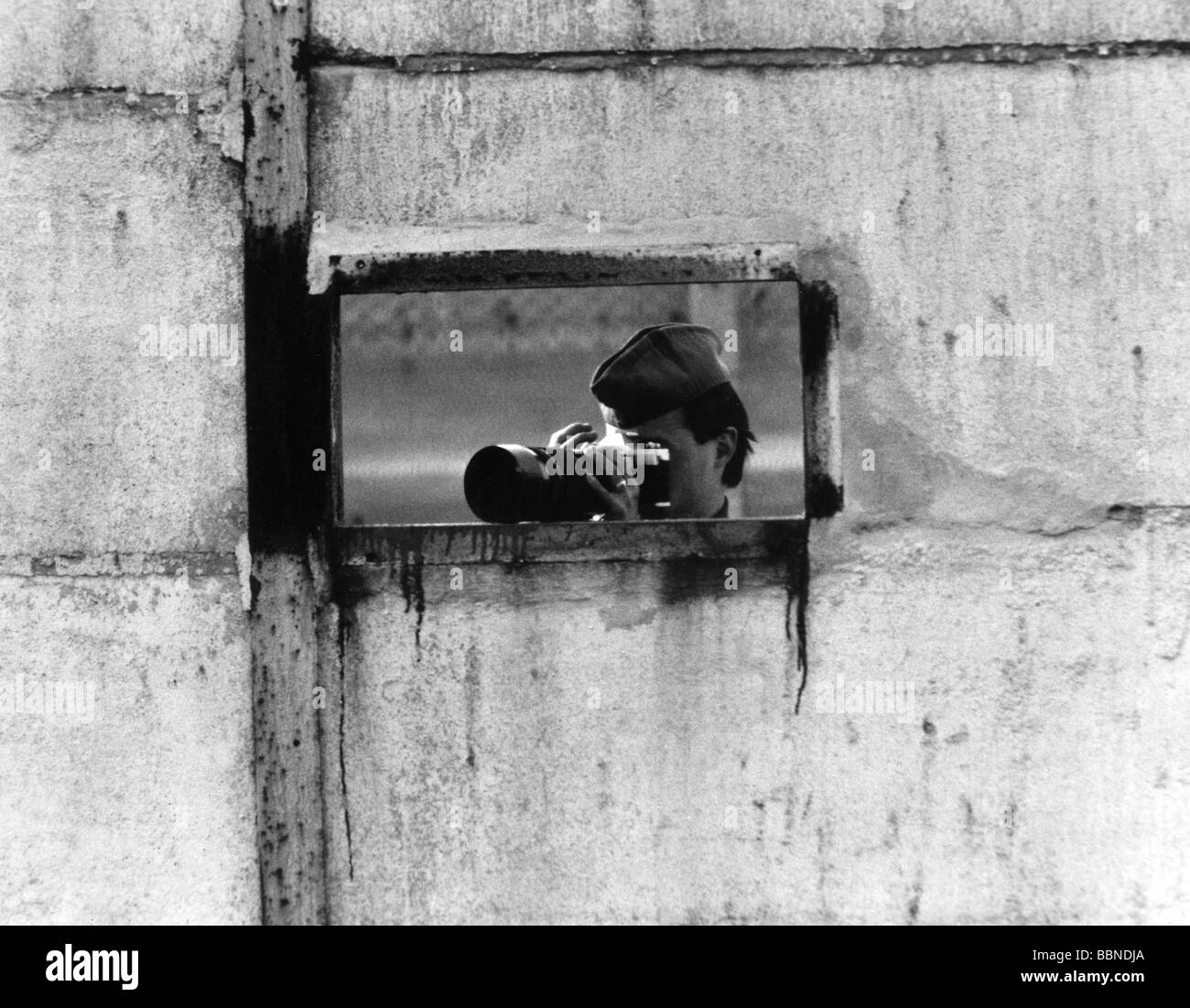 geography / travel, Germany, GDR, border, soldier taking photos through a hole in the Berlin Wall, 1980s, Additional - Stock Image