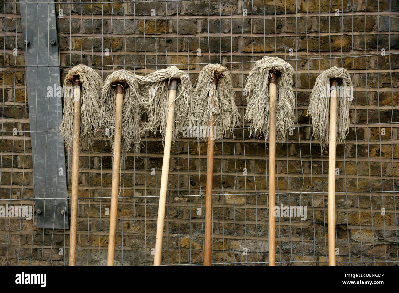 Six floor mops in a row, east London, UK - Stock Image