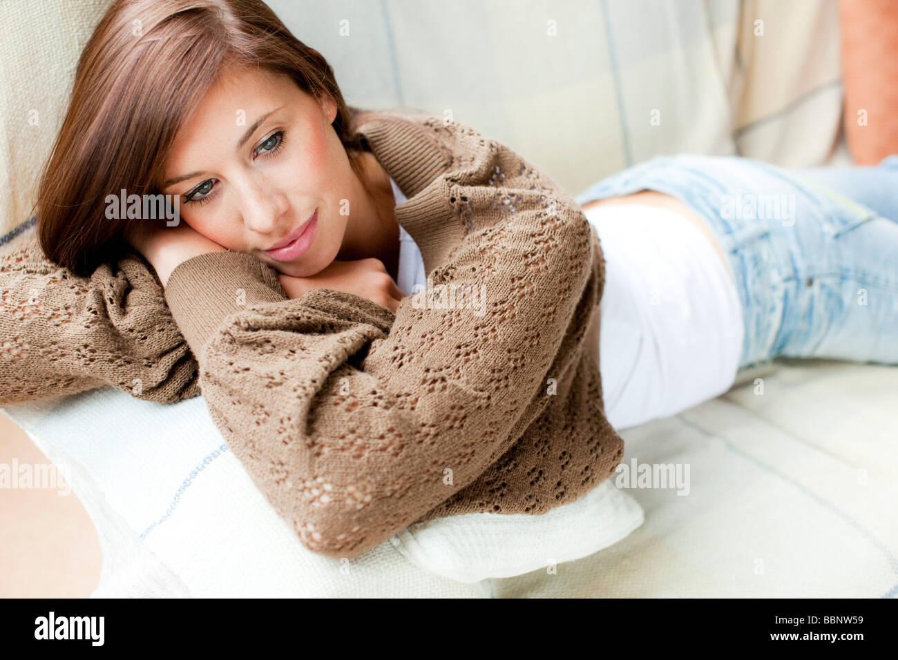 Woman lying on sofa - Stock Image