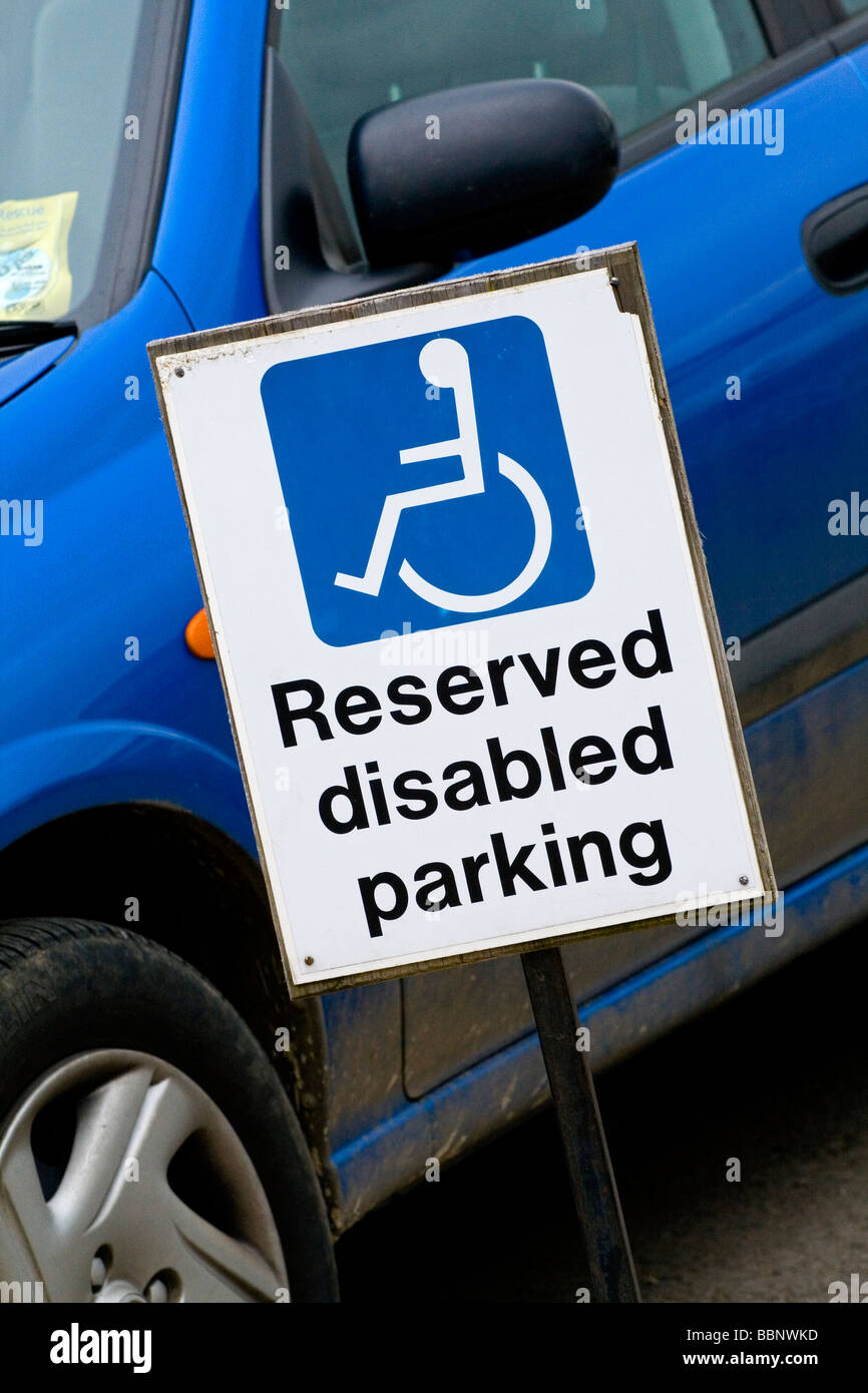 Reserved Disabled Parking sign next to blue car in car park - Stock Image