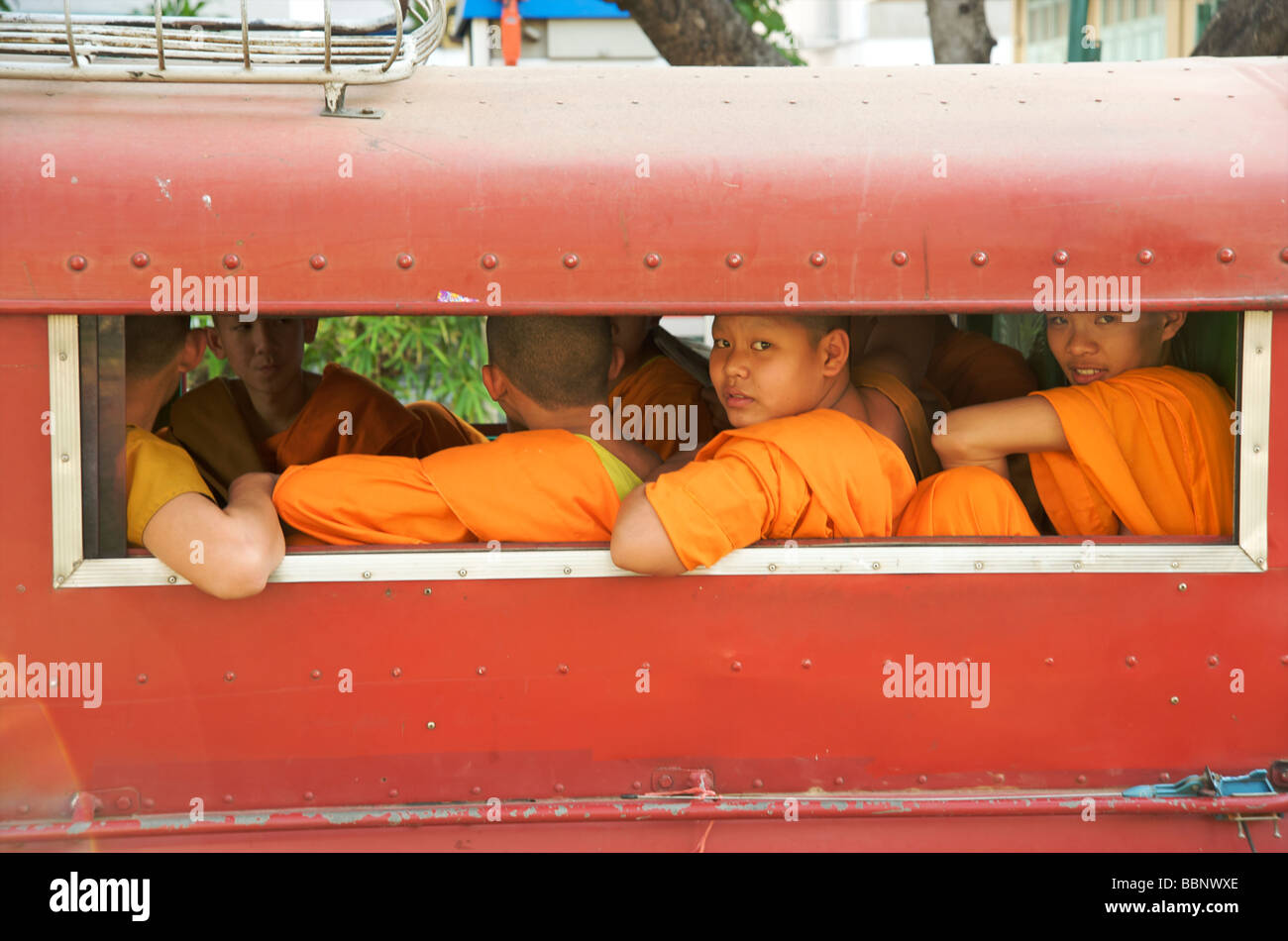 Thai Buddhist monks aboard a pick up truck known as a songthaew,two looking out the window in Chiang Mai Thailand - Stock Image