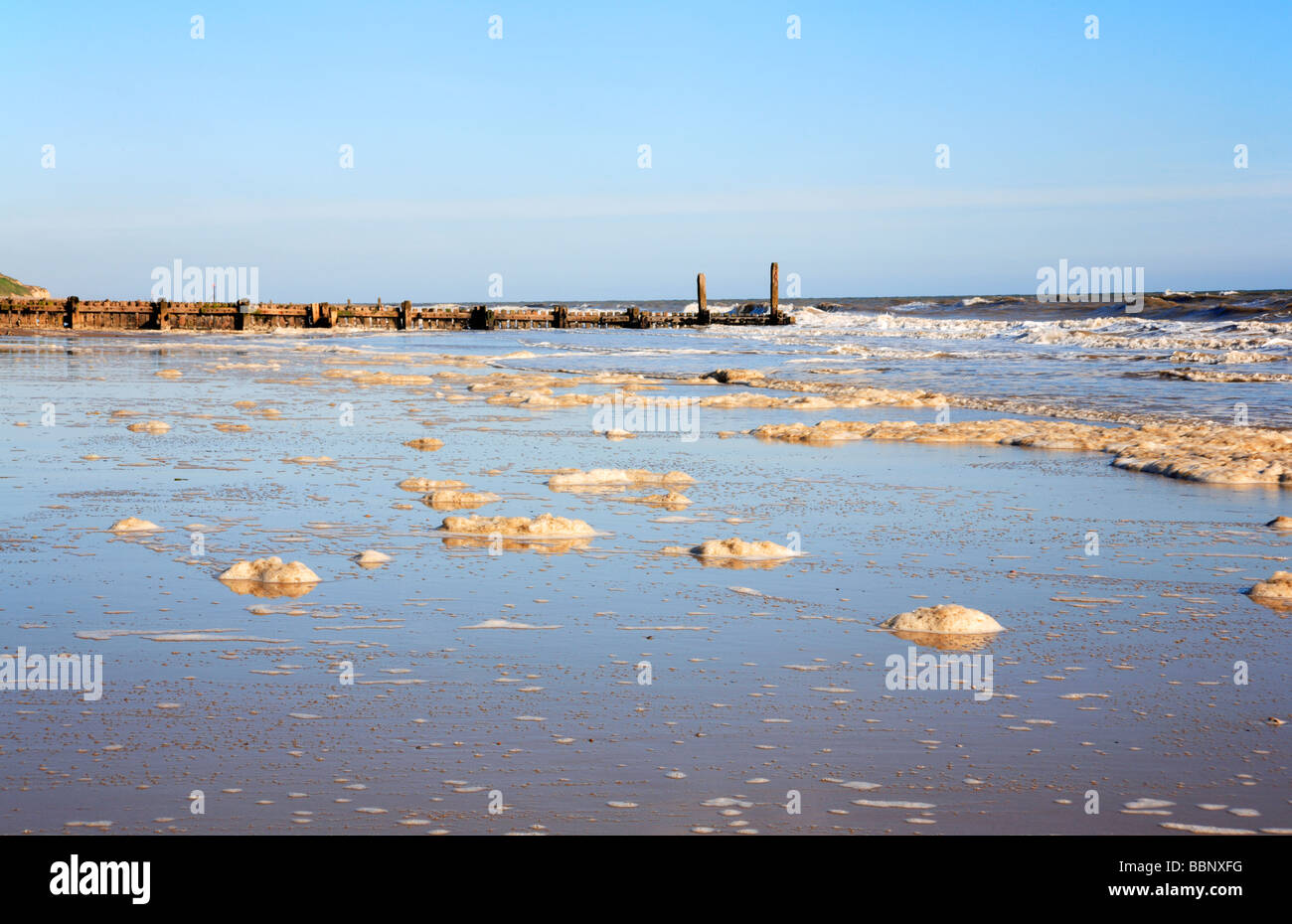 Spume on the beach at Mundesley, Norfolk, United Kingdom. - Stock Image