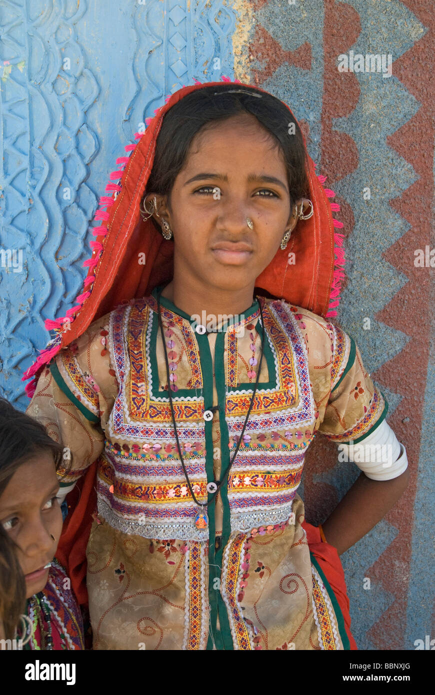 Kutchi girl in tribal costume leaning against bhunga wall, Hodka, Gujarat, India - Stock Image