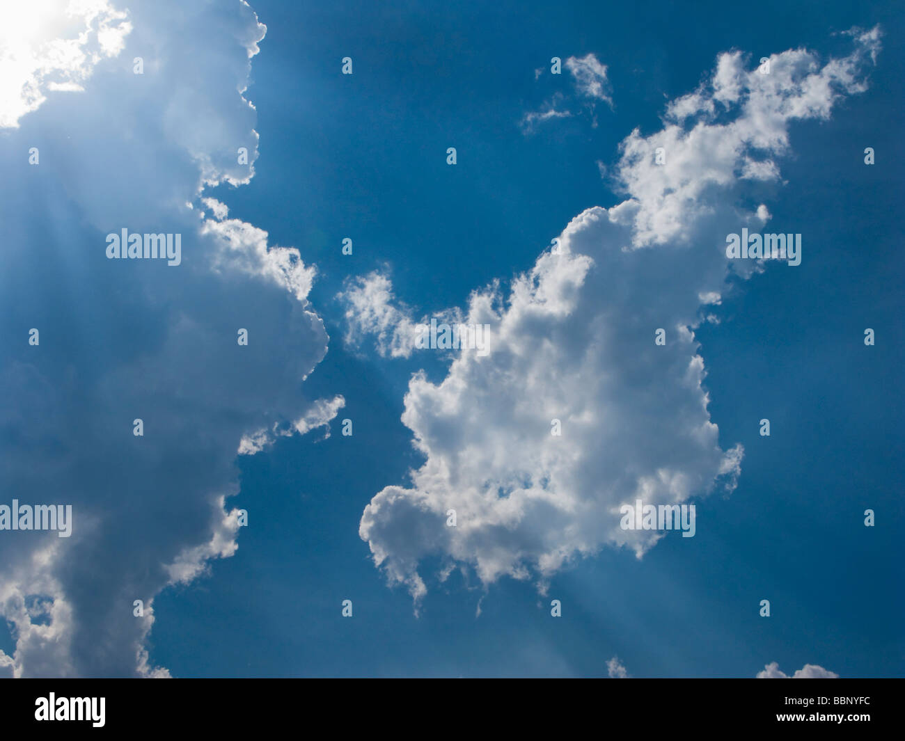 Blue sky with fluffy white clouds and sun rays - Stock Image