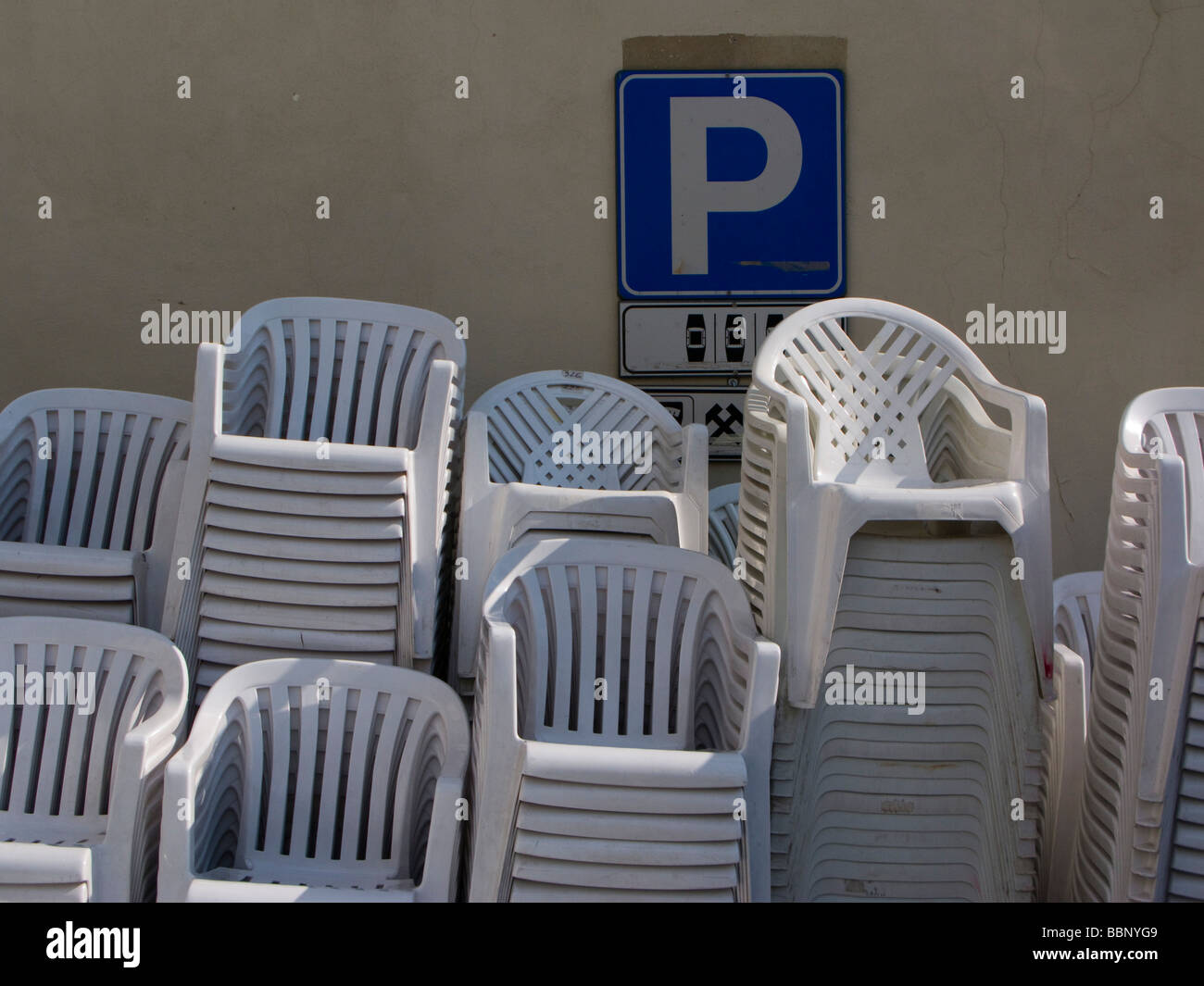 Stacked plastic chairs beneath parking sign - Stock Image