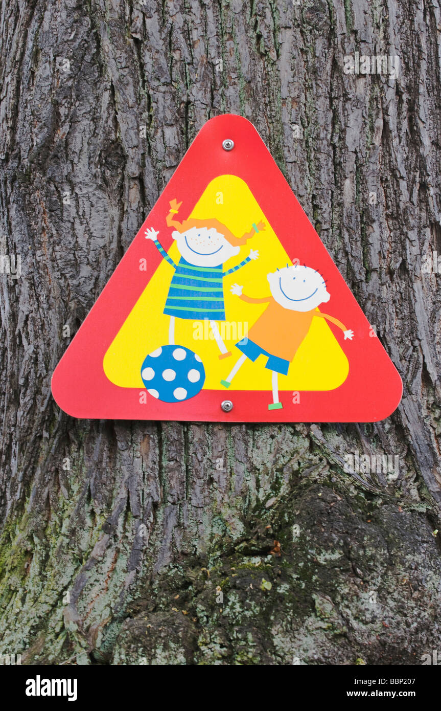 Sign, Attention, children playing, on tree trunk - Stock Image