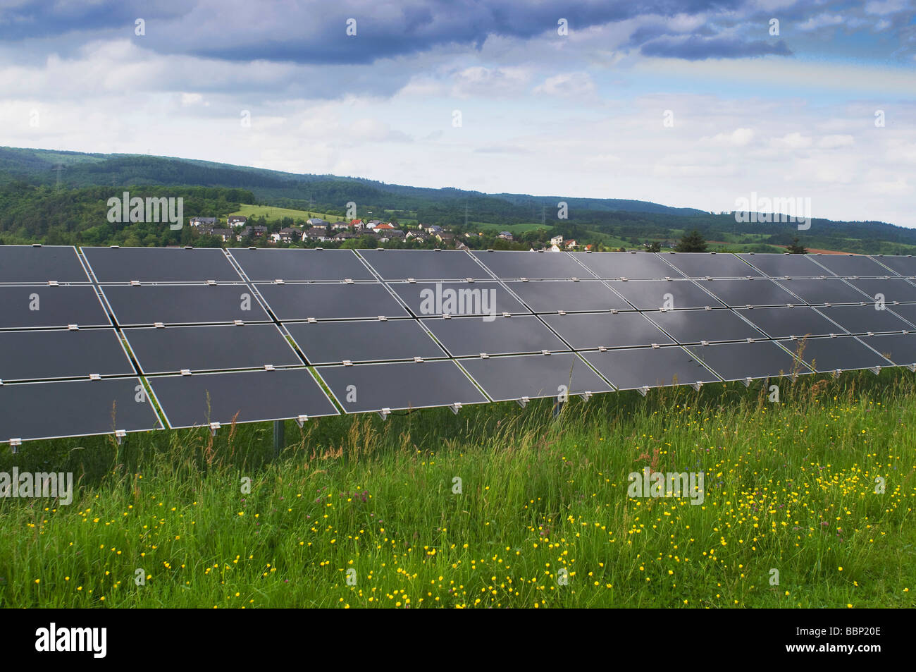 Solar power plant on a green field, photovoltaic system, view of a series of several modules - Stock Image