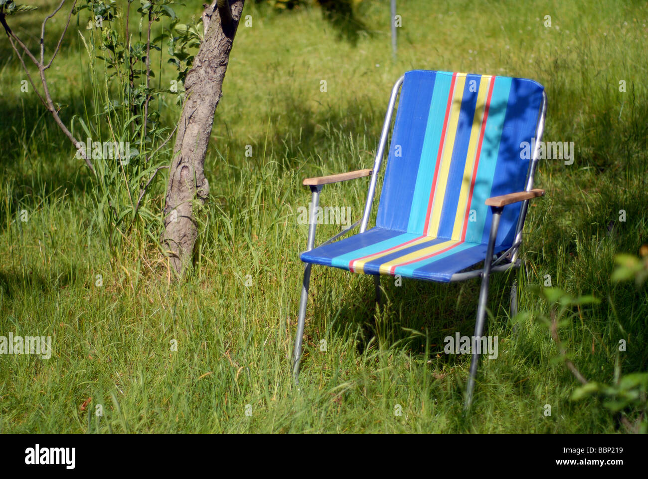 A retro 1970's deck chair on an overgrown lawn in summer - Stock Image