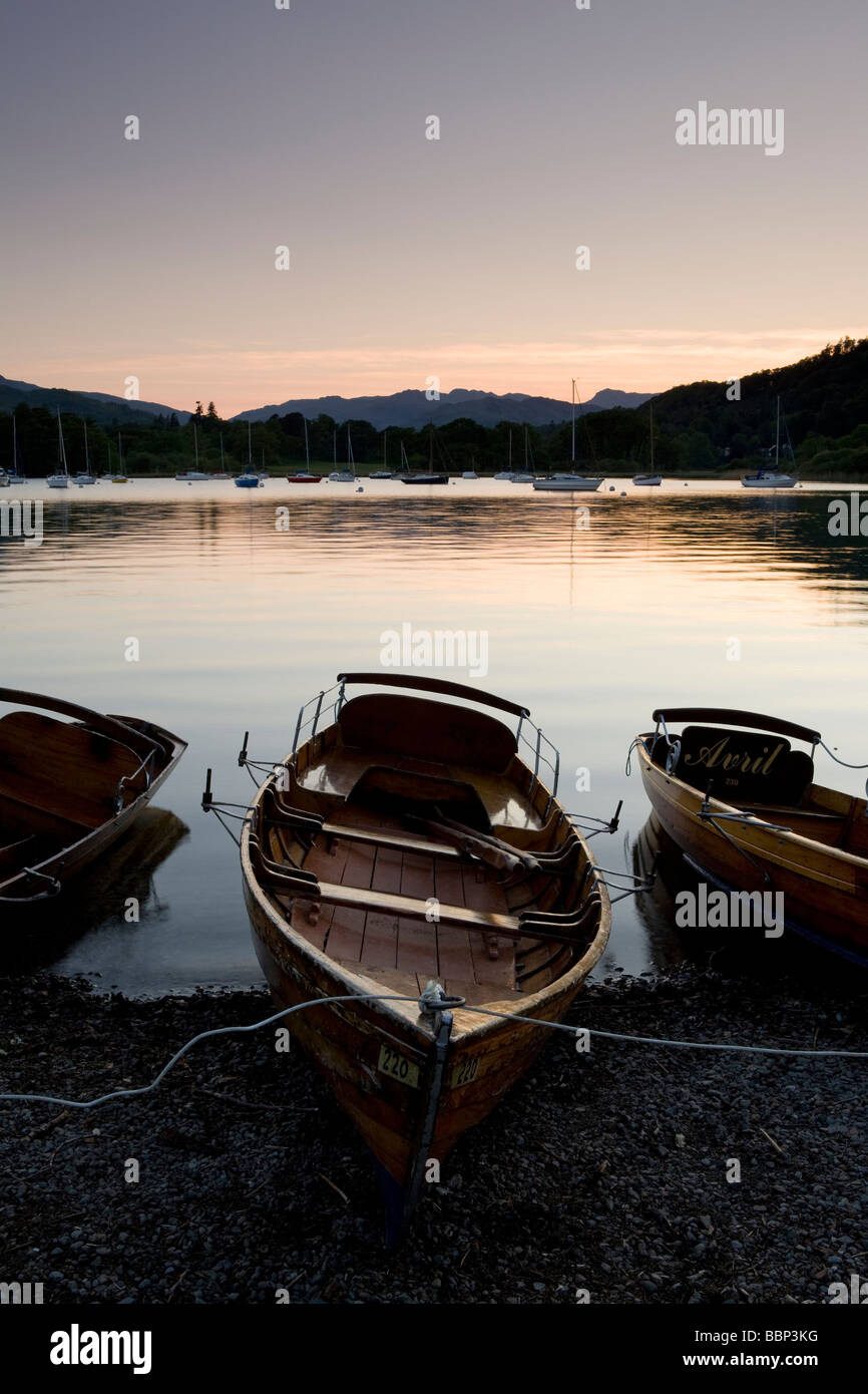 Boats on the bank of Lake Windermere in the Lake District at sunset - Stock Image
