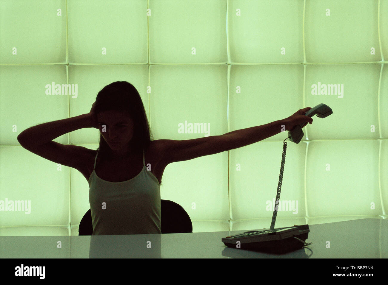 Woman at desk, holding head, holding phone receiver away - Stock Image