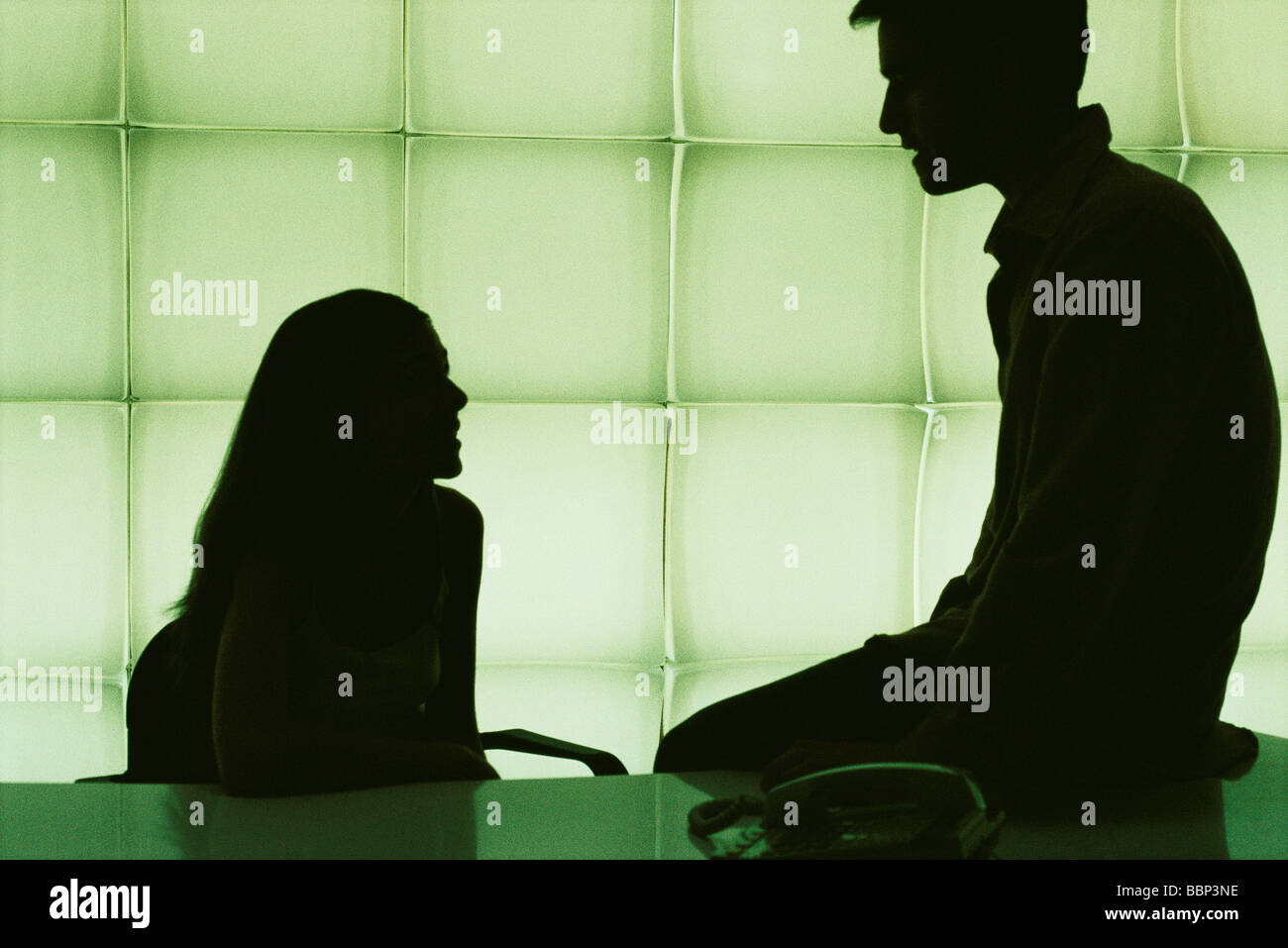 Colleagues chatting, man sitting on corner of desk, woman sitting at desk - Stock Image