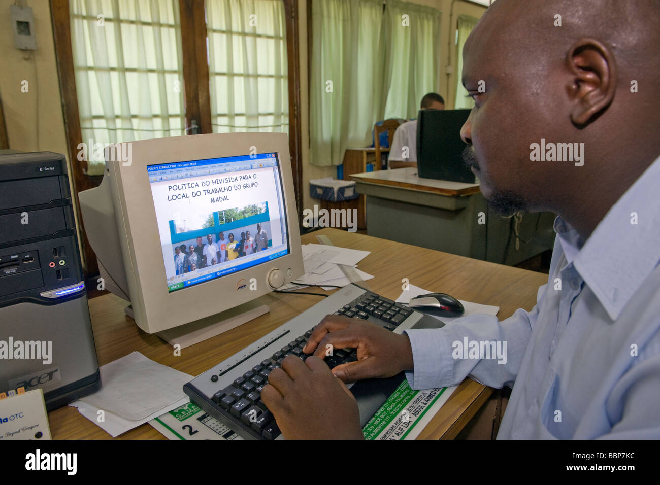 HIV AIDS Programme coordinator working at his computer Quelimane Mozambique - Stock Image