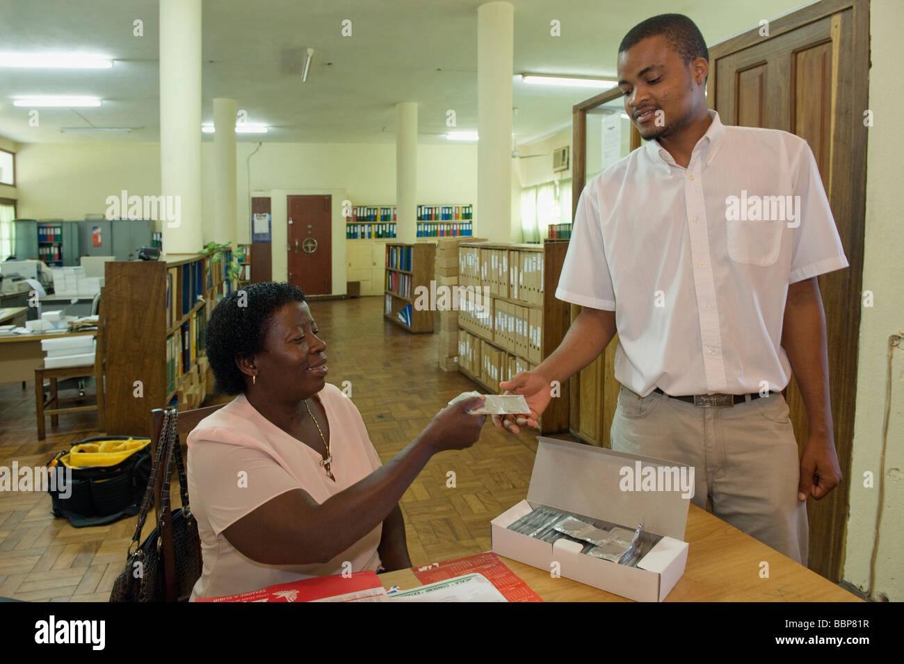 A secretary distributes free condoms to office staff Quelimane Mozambique - Stock Image