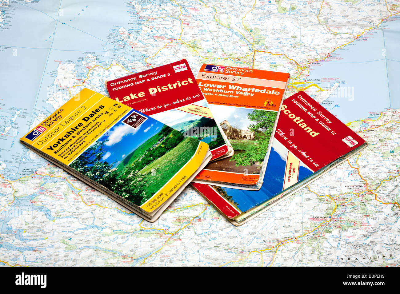 Set of four Ordnance Surveys maps on a map of Scotland - Stock Image