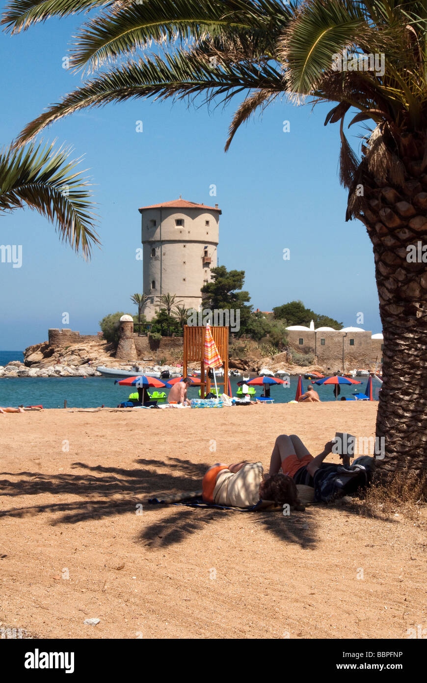 A couple laze reading books in the shade of palm tree at Giglio Campese the beach on the Island of Giglio or Isola - Stock Image