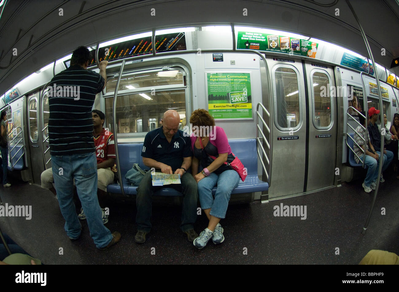 Reading The New York City Subway Map.Tourists On The Subway Reading A Map In New York On Sunday May 24