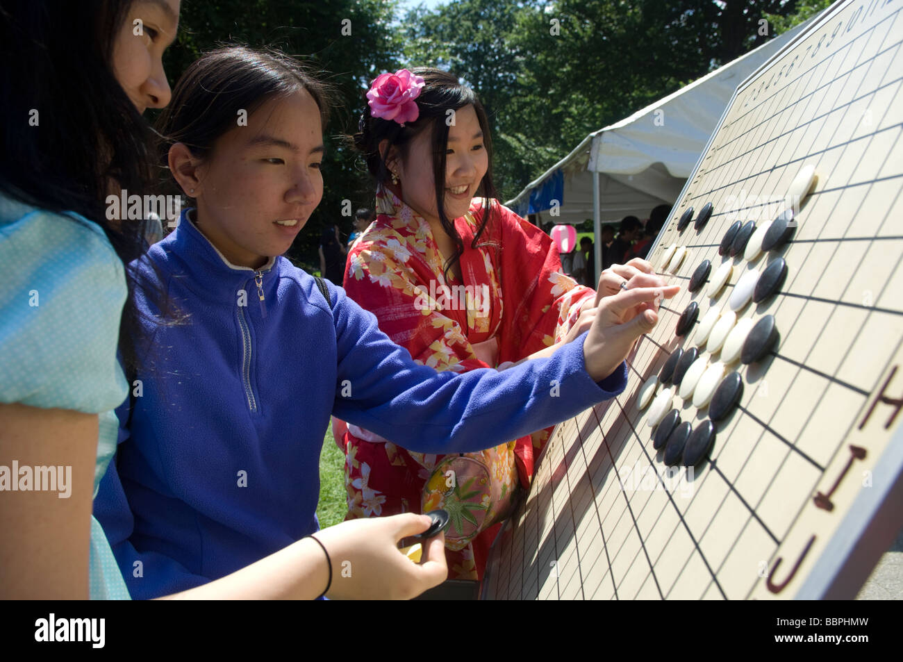 Girls check out a Japanese board game called Go or Japanese checkers Stock Photo