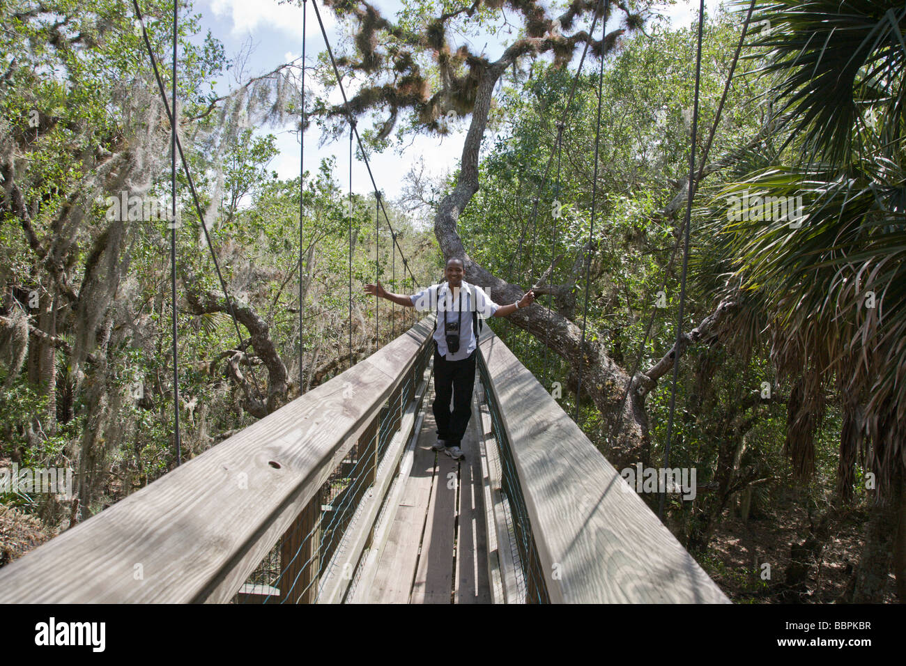Idrissa Abdou, a tourist from Maryland, crosses the canopy walkway leading to the tower at Myakka River State Park Stock Photo