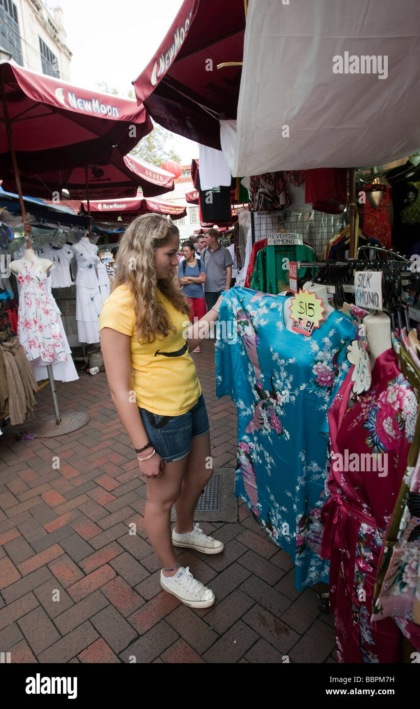 Tourist is interested in a dress, Chinatown, colorful market as a tourist attraction, Temple Street, Singapore, - Stock Image