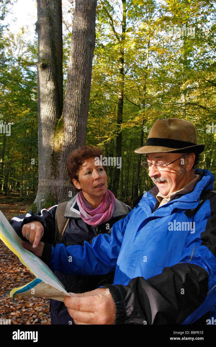A COUPLE OF SENIOR CITIZENS WITH A TOPOGRAPHICAL MAP FOR A WALK IN THE FOREST OF SENONCHES, EURE-ET-LOIR (28), FRANCE - Stock Image