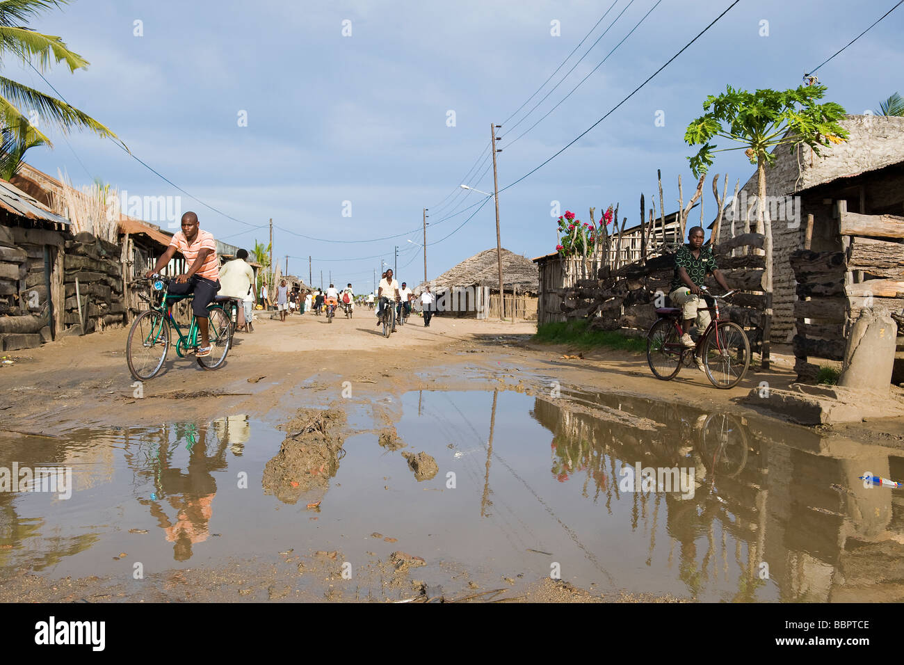 Road with water filled potholes provide breeding grounds for Malaria mosquitoes Quelimane Mozambique - Stock Image