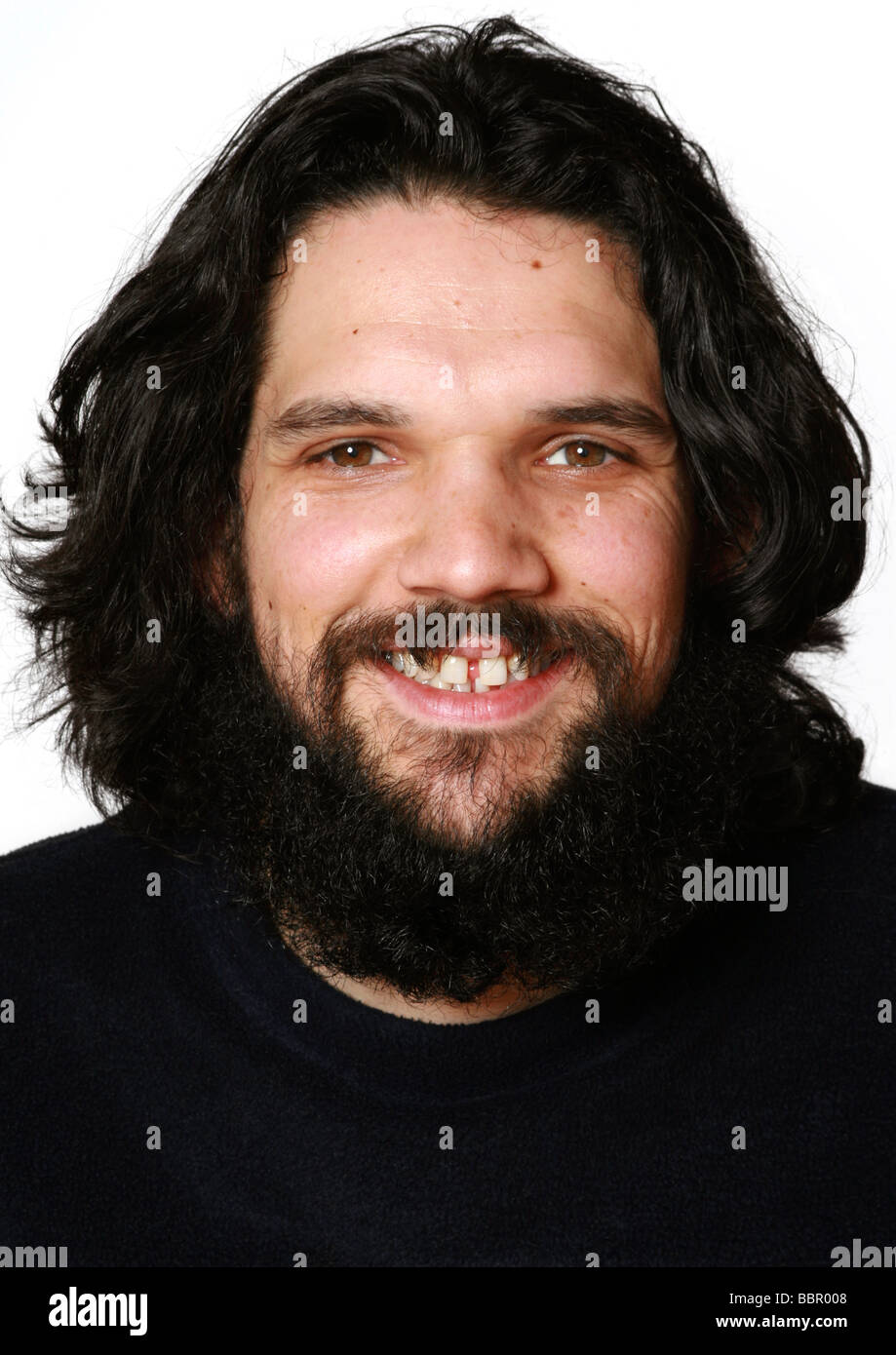 Long-haired man with beard and toothy grin - Stock Image