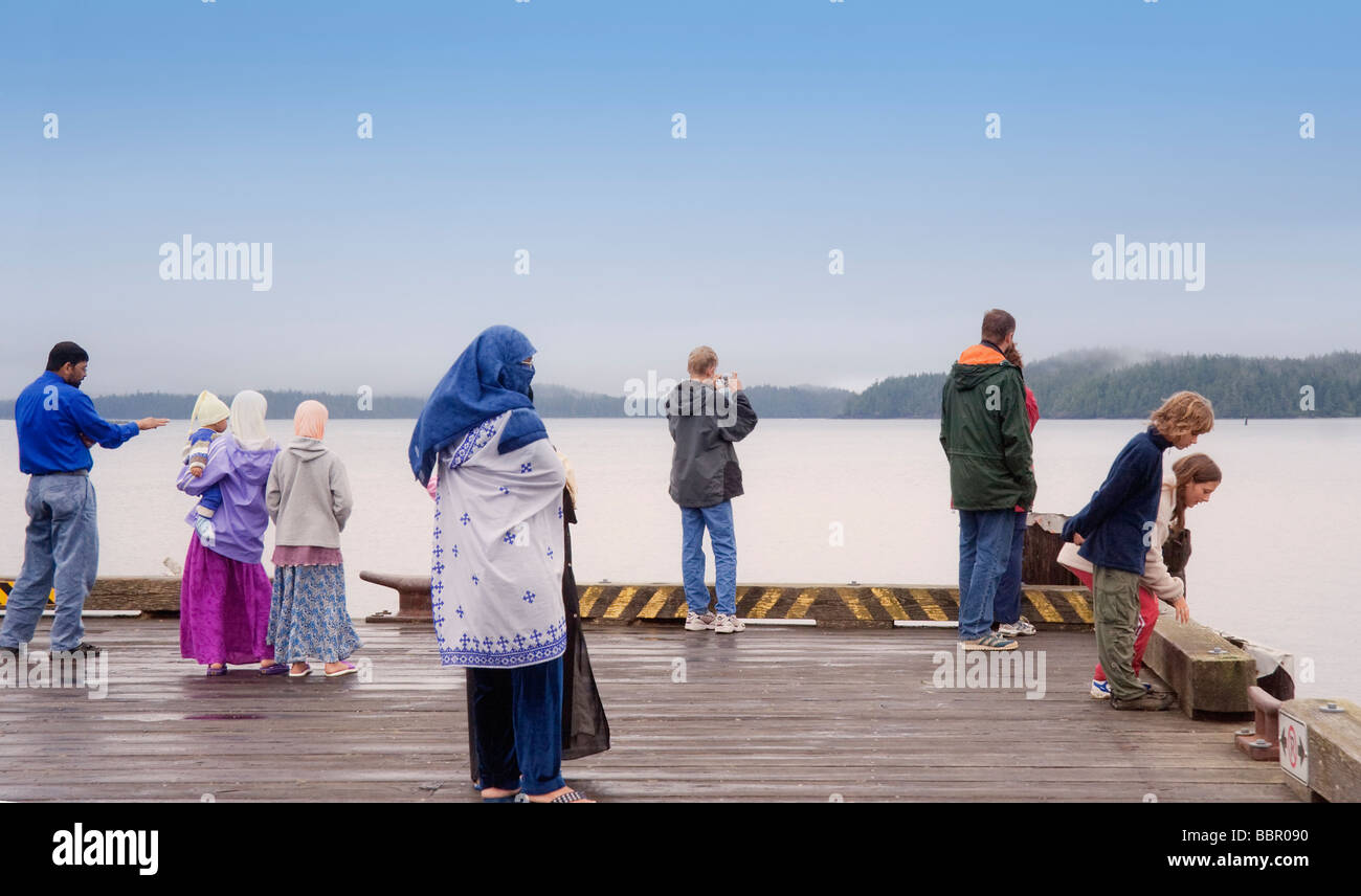People of different Nationalities on Jetty enjoying view over Pacific Ocean - Stock Image