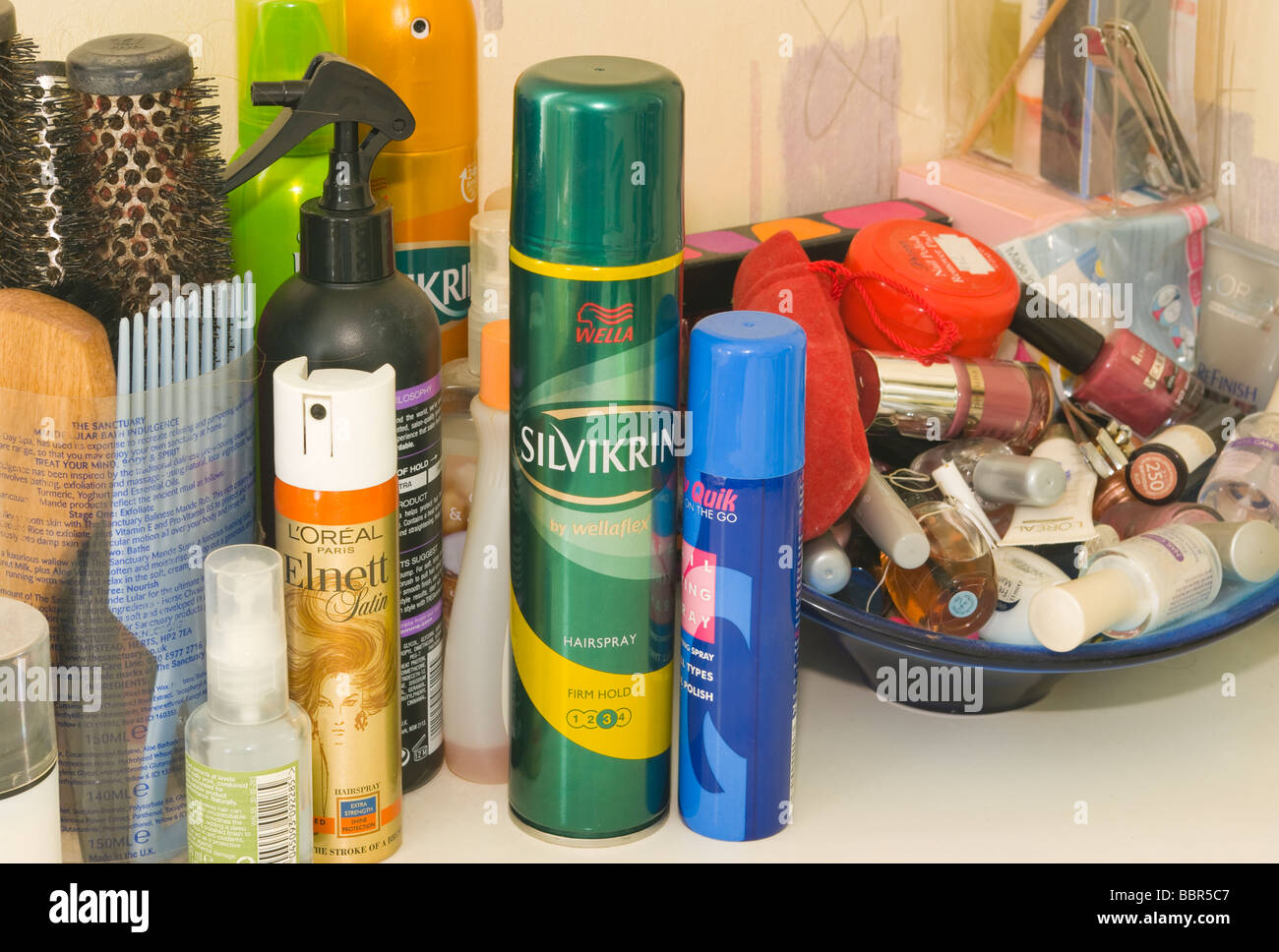 Brushes Hair Care Products and Make Up On a Ladies Dressing Table - Stock Image