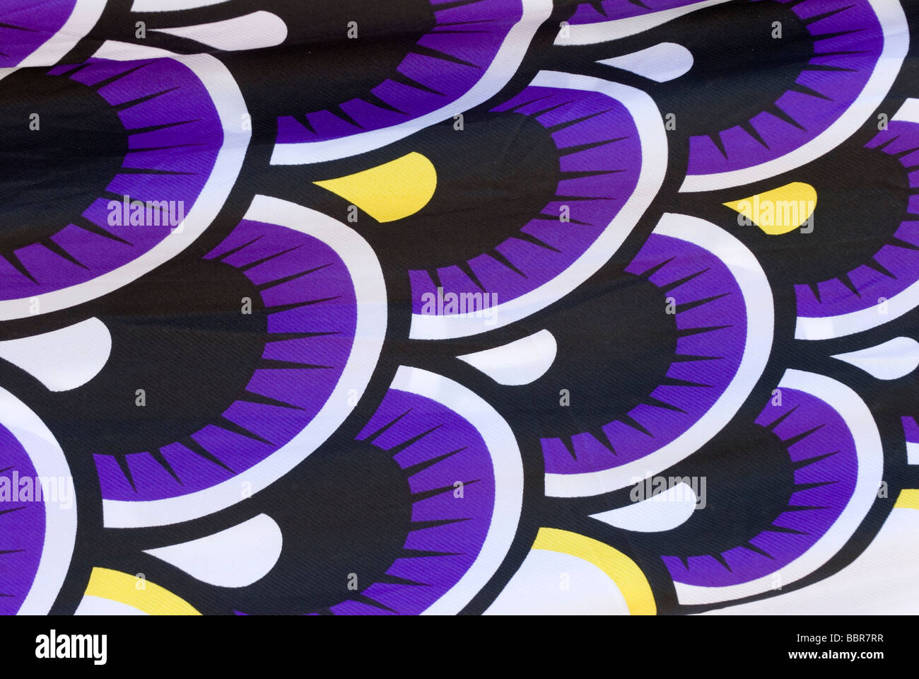 A close up shot of a fabric carp windsock or koinobori streamer showing a fish scale pattern in purple, white, black - Stock Image