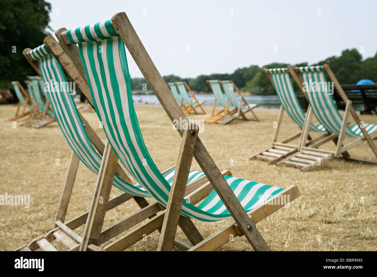 Empty deck chairs in the park on parched brown grass by a lake in the summer time - Stock Image