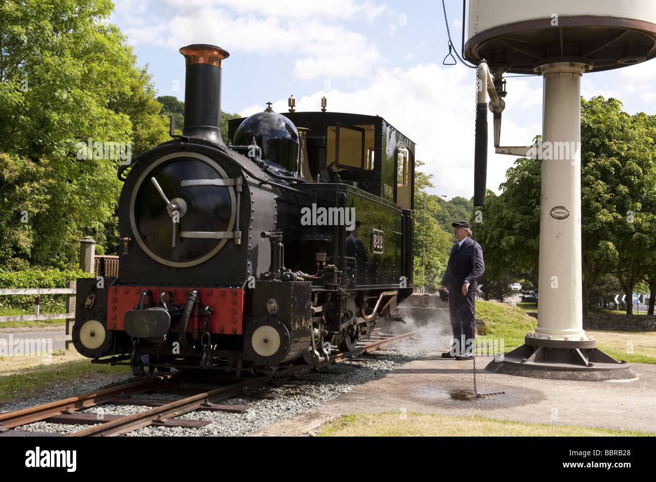 Steam Engine 'Earl' filling up with water at station platform water tower on working narrow gauge railway - Stock Image