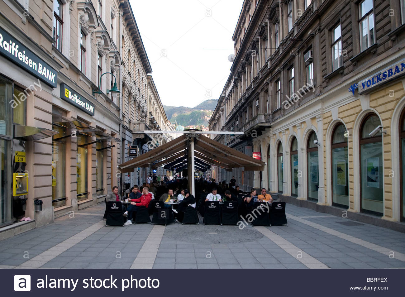 People sitting in a coffeehouse along the main pedestrian street Ferhadija in Sarajevo capital of Bosnia Herzegovina - Stock Image