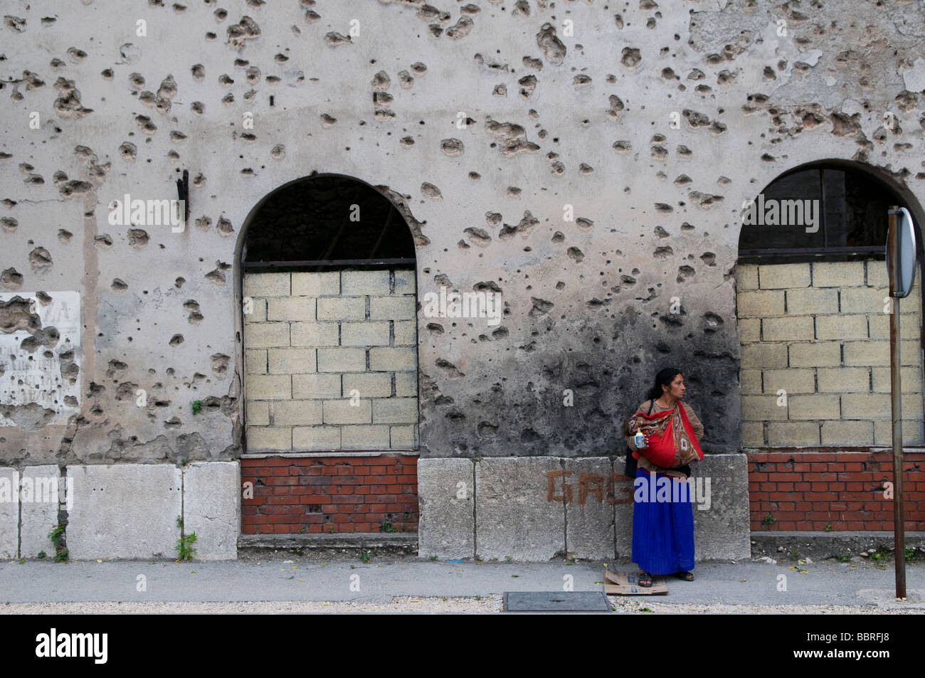 A gypsy woman stands in front of a house showing shrapnel damage from the 1992-95 war in the town of Mostar in southern - Stock Image