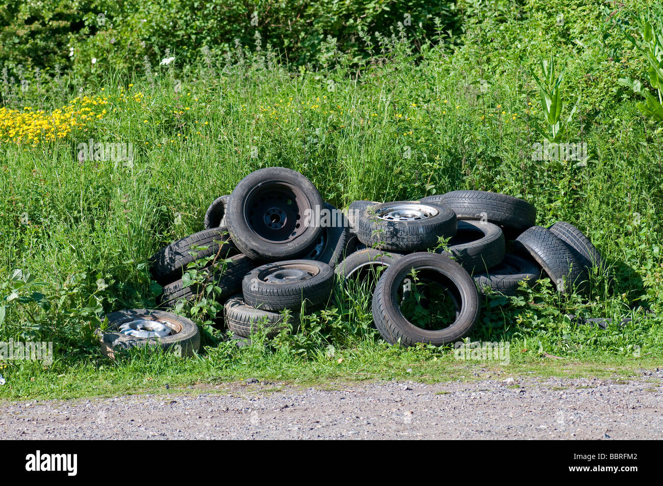 Illegal fly tipping. Abandoned tyres in car park of nature reserve - Stock Image