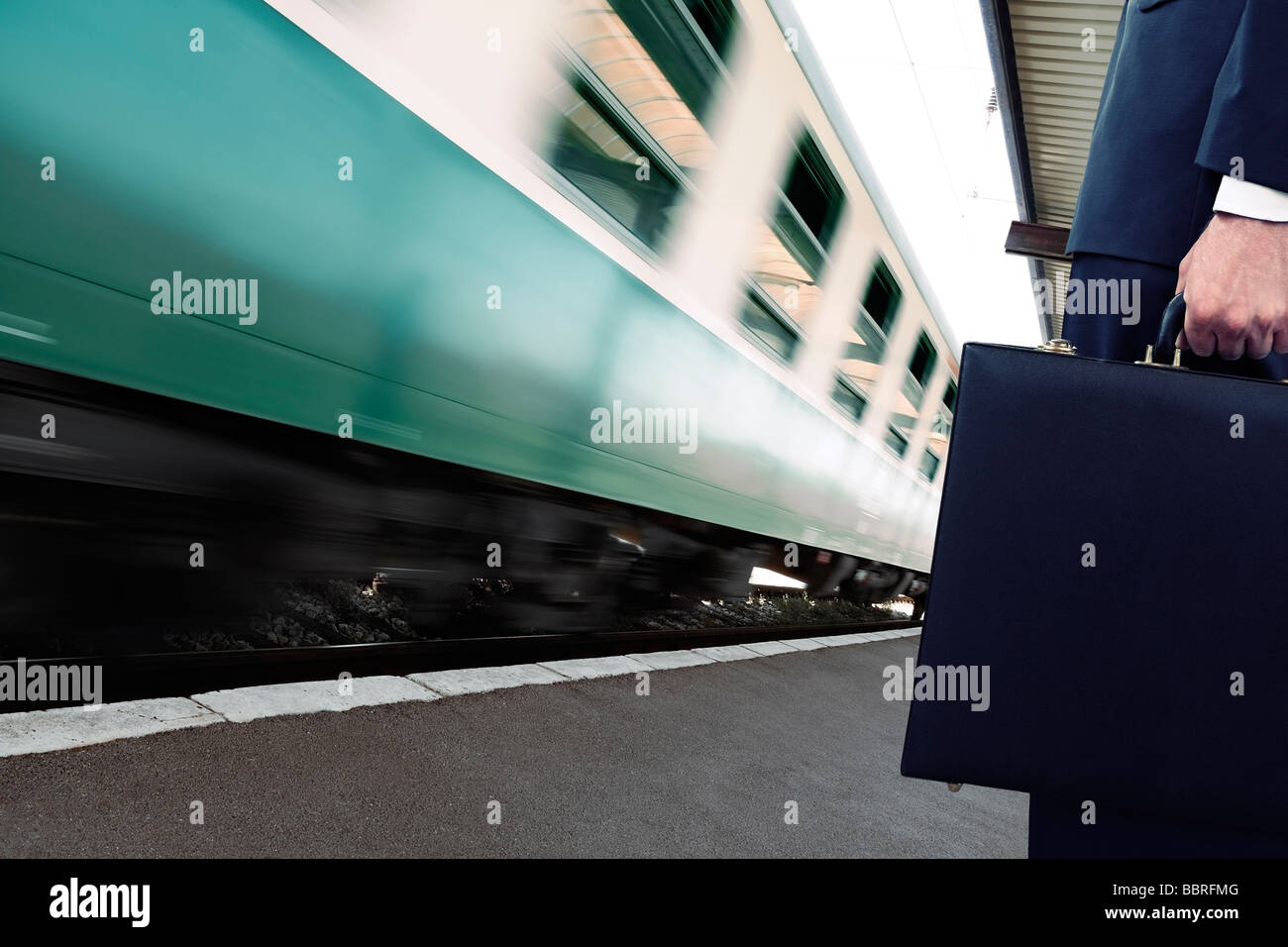 Commuter Standing on a Train Station Platform as a Train Goes Past Low Section - Stock Image