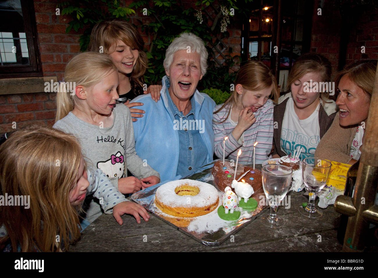 Grandmother 70th birthday surrounded by 5 smiling grandchildren Mickleton UK - Stock Image
