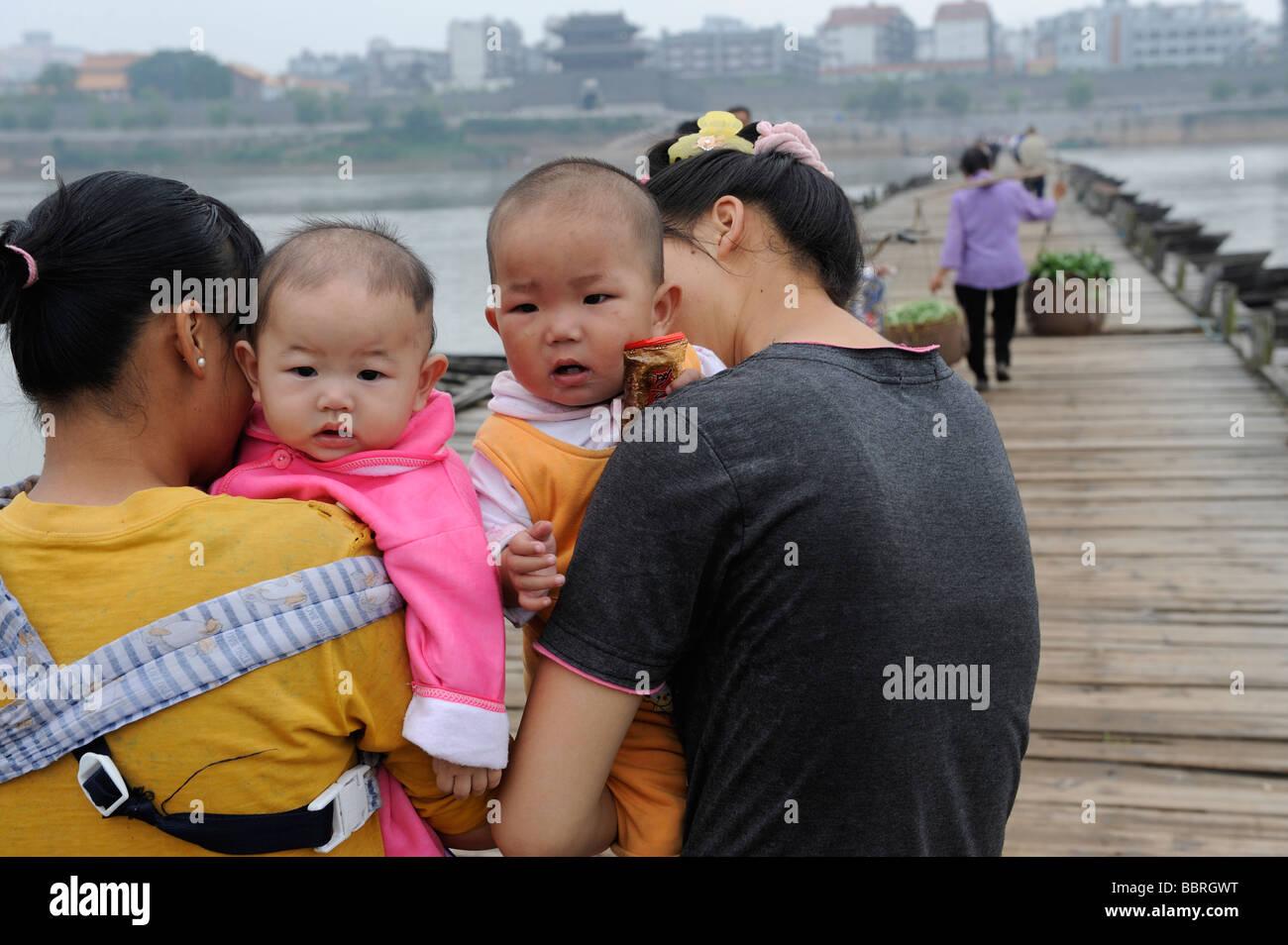 Chinese mothers hold babies in Ganzhou, Jiangxi, China. 11-Jun-2009 - Stock Image