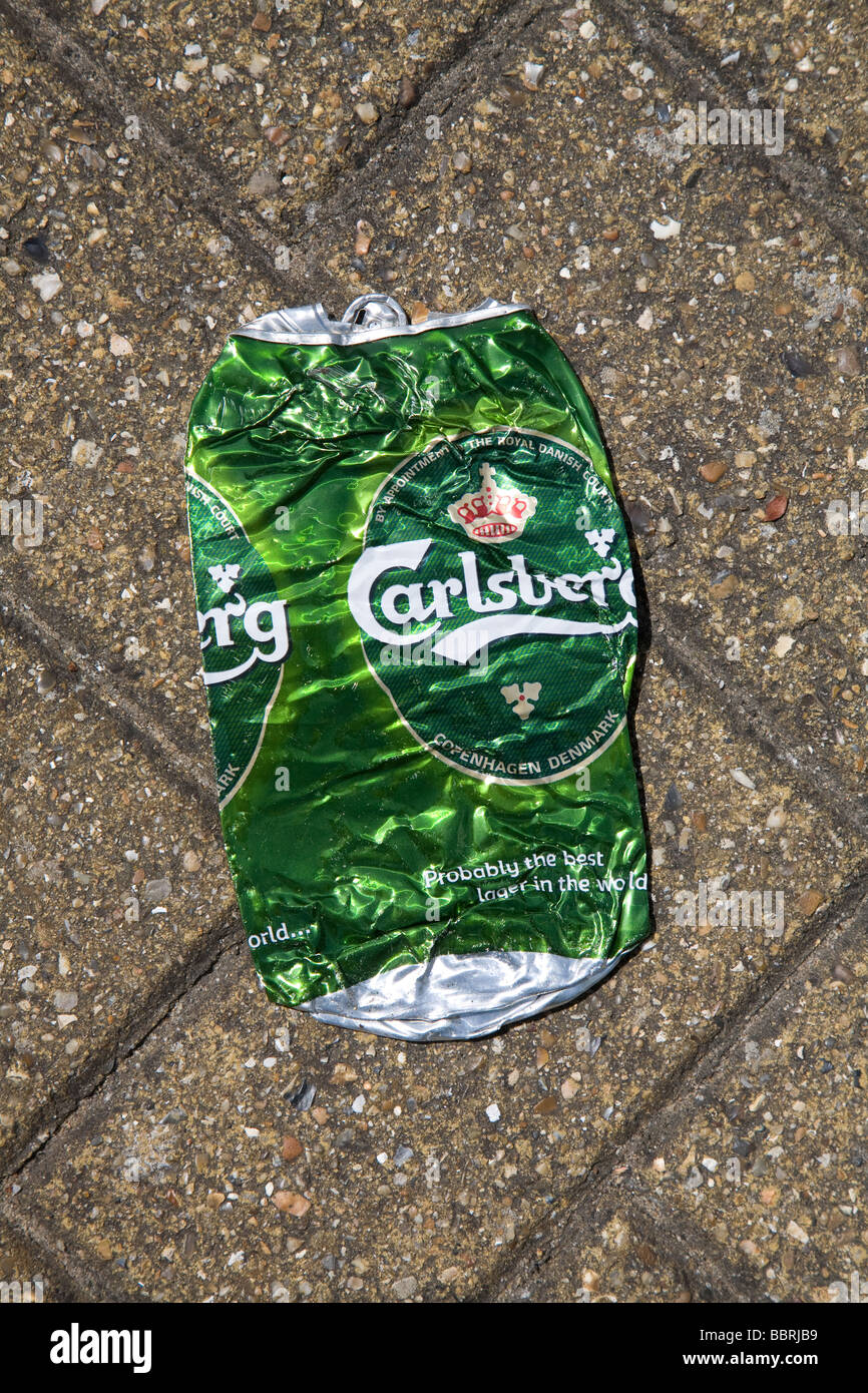 Crumpled squashed Carlsberg beer can on ground - Stock Image