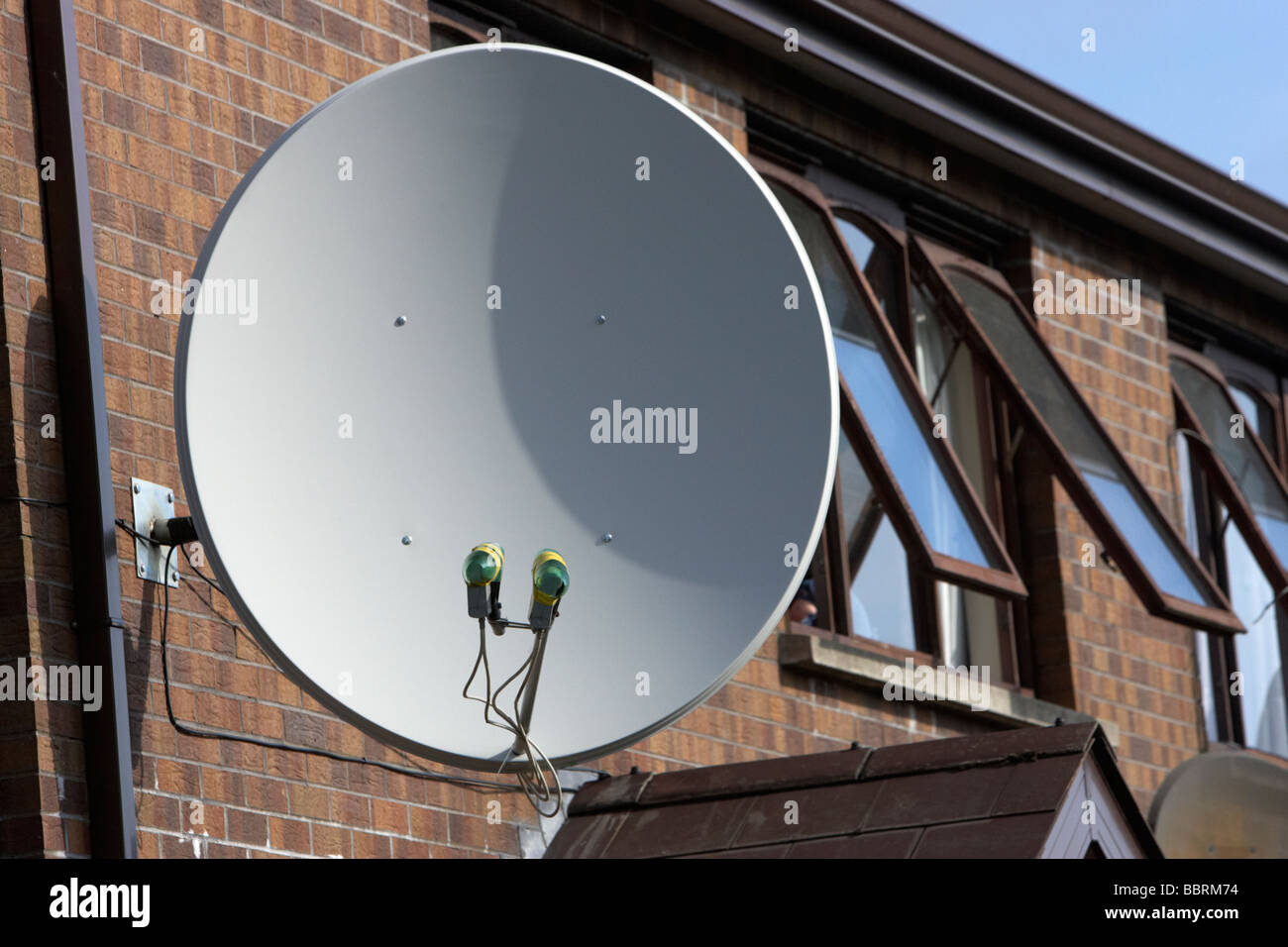 large satellite dish attached to the outside of a row of houses in the uk - Stock Image