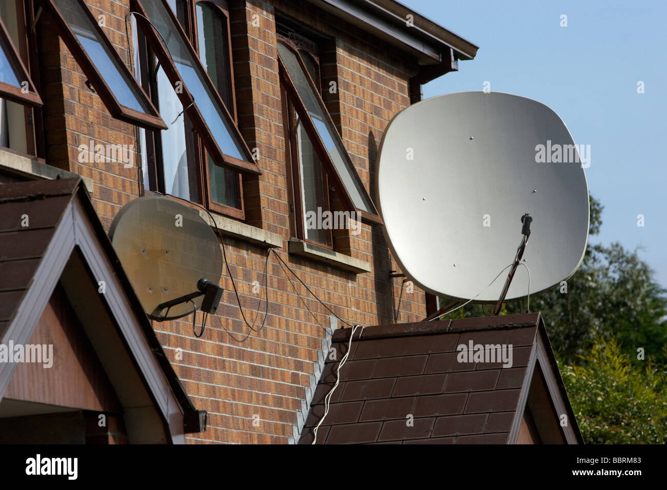 large satellite dishes attached to the outside of a row of houses in the uk - Stock Image
