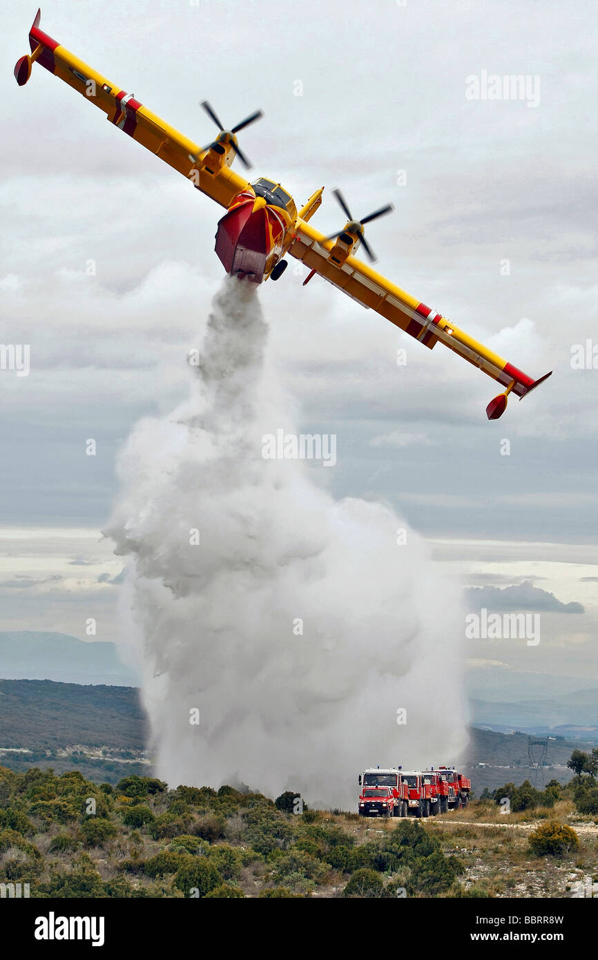 CANADAIR CL 415 PELICAN DROPPING THE WATER FROM ITS HOLD AS PROTECTION FOR A FOREST FIRE FIREFIGHTING GROUP, FOURNES, - Stock Image
