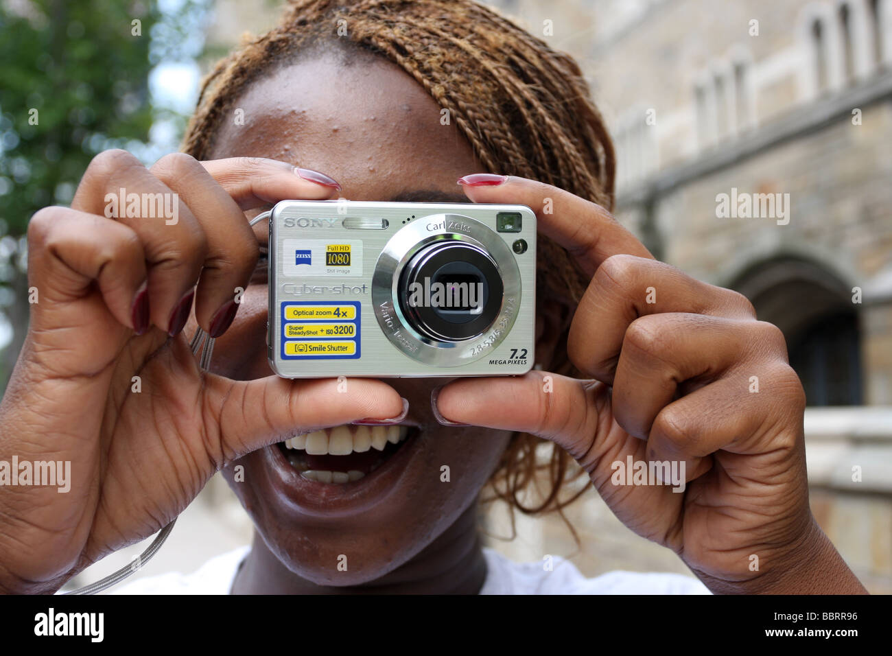A woman takes a digital photo with a compact digital camera - Stock Image