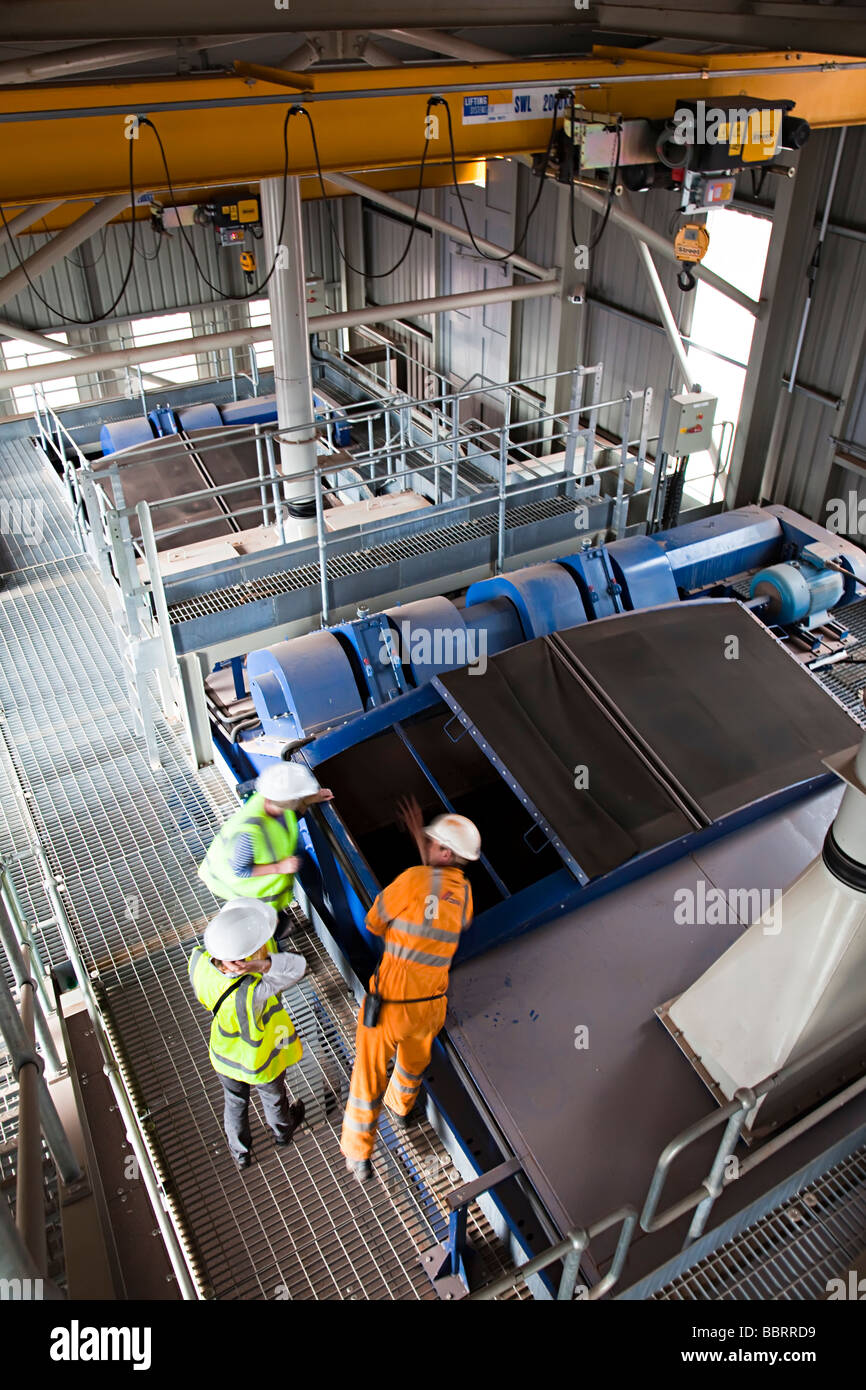 Three people wearing safety clothing inspecting crushing machinery in limestone quarry plant near Cardiff Wales - Stock Image