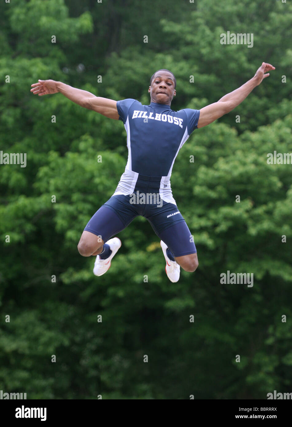 A High School track athlete performs the long jump during the State Championship track meet in New Haven CT USA - Stock Image