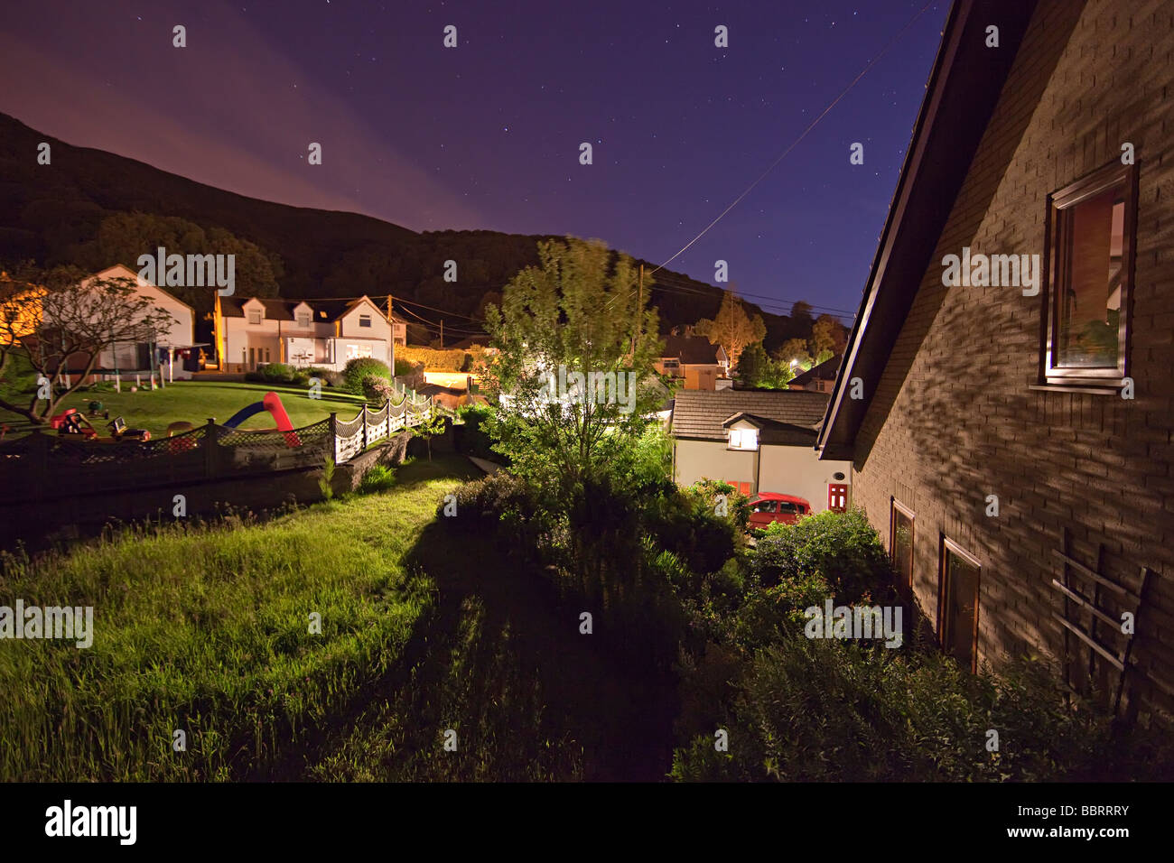 House garden and buildings in village at night with light from street lamps Llanfoist Wales UK - Stock Image