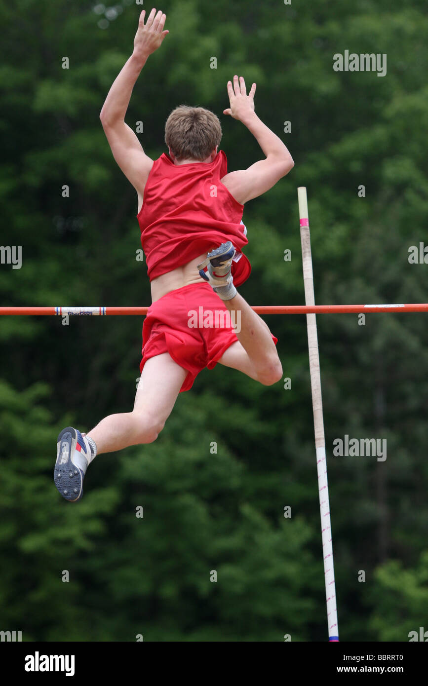 A pole vaulter clears the bar - Stock Image