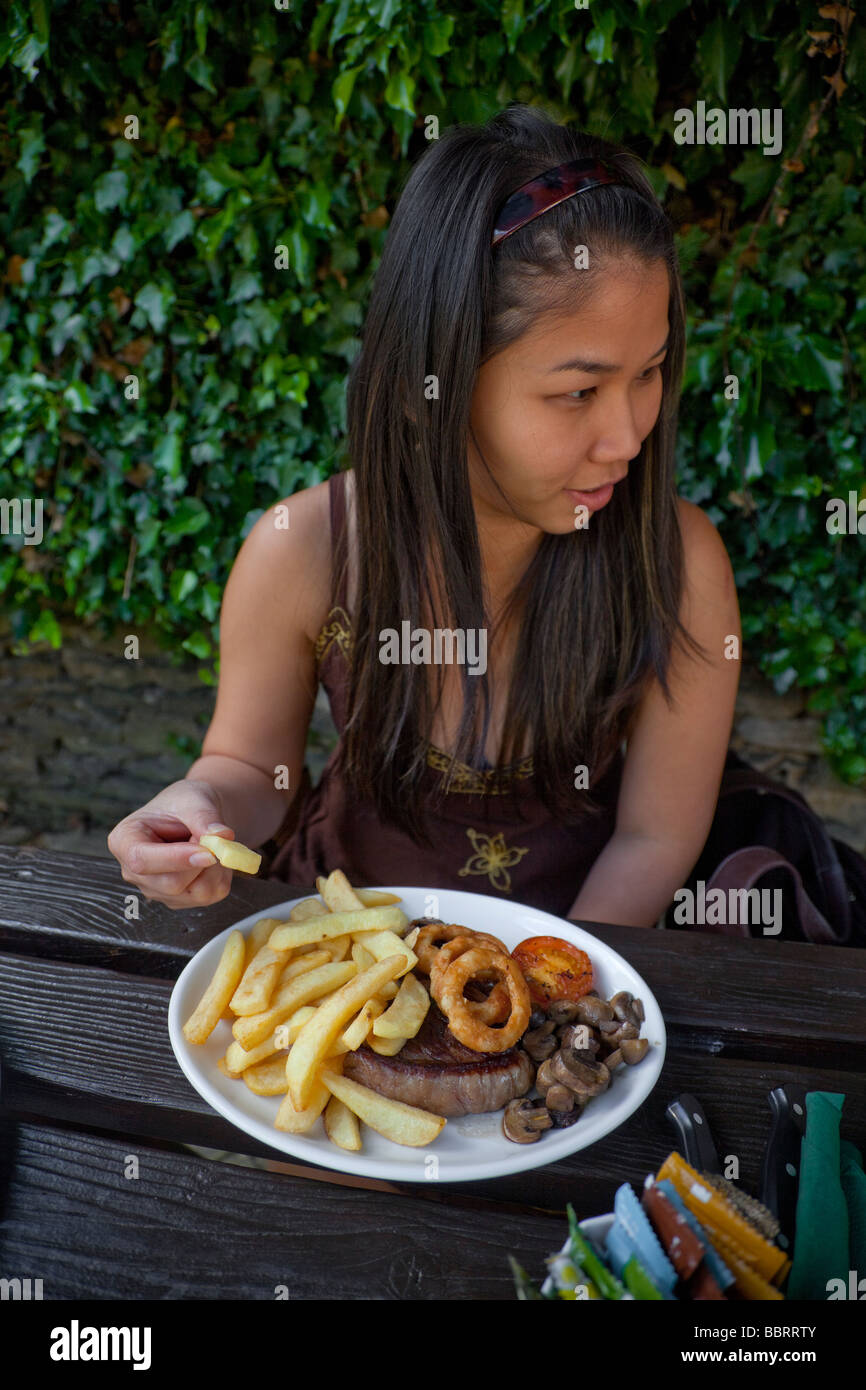 Oriental tourist lady trys her first Western steak and chips meal - Stock Image