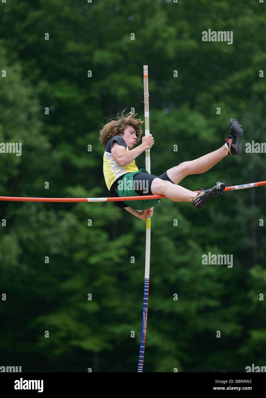 A high school athlete misses clearing the bar during the High School State Championship Track and Field meet in - Stock Image