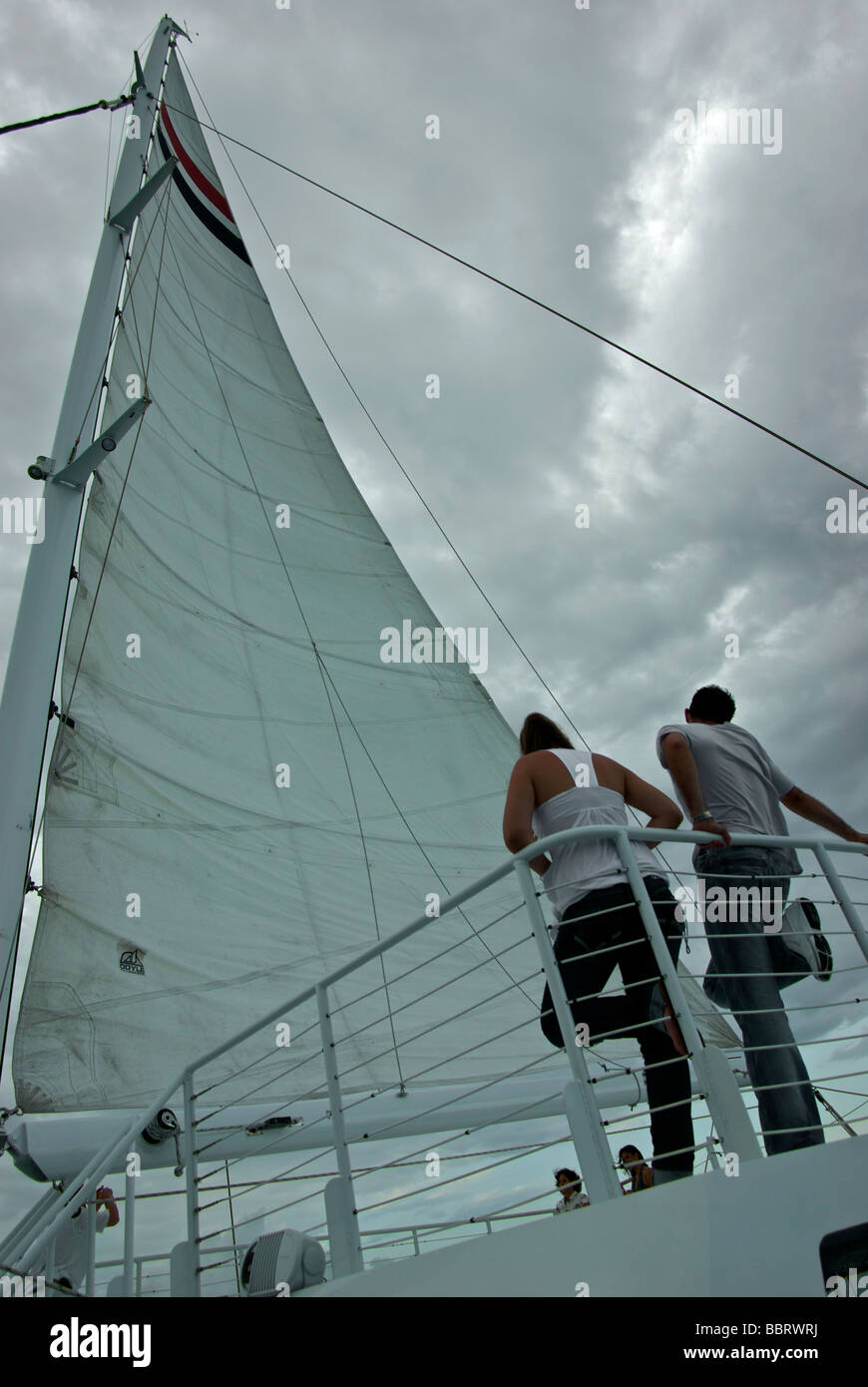 Couple leaning against catamaran charterboat top deck railing looking at mainsail against backdrop of storm clouds - Stock Image